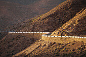 Lonely country road winding through barrren landscape, Fuerteventura, Canary Islands, Spain