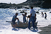 A family of fishermen landing their catch in the surf of the black sand beach of Ajuy, Fuerteventura, Canary Islands, Spain