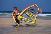 Athletic sailboarder holding his board and sail at the beach Playa Barca, Playa de Sotavento, Jandía Peninsula, Fuerteventura, Canary Islands, Spain