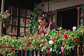Young woman watering geraniums on the wooden balcony of an old house in Comillas, Cantabria, Spain