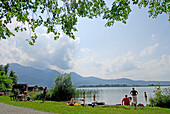 bathers at shore of lake Kochelsee, Bavarian Alps in background, Upper Bavaria, Bavaria, Germany