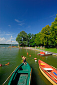 Two children fishing and rowing boats at beach of lake Simssee, Chiemgau, Upper Bavaria, Bavaria, Germany