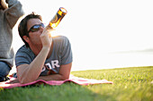 Man lying on blanket while drinking a bottle of beer, Ambach, Lake Starnberg, Bavaria, Germany