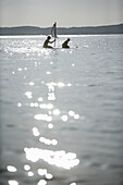 Two kids on a small raft with sail, Ammerland, Lake Starnberg, Bavaria, Germany