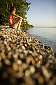Frau sitzt mit einem Glas Wein am Seeufer vom Starnberger See, Ammerland, Bayern, Deutschland, MR