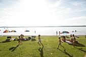 Leute beim Sonnenbaden, Kinder beim Spielen, Seeufer, Buchscharn, Starnberger See, Bayern, Deutschland