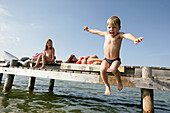 Boy jumping from jetty into water, Karnifflbach, Lake Starnberg, Bavaria, Germany, MR