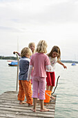 Children playing on jetty at Lake Woerthsee, Bavaria, Germany, MR