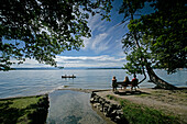 Three people sitting on the lakeshore, kanu in the background, Tutzing, Lake Starnberg, Bavaria, Germany