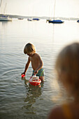 Boy playing with toy boat in Lake Woerthsee, Bavaria, Germany, MR