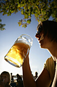 Mid adult woman drinking beer, beer garden of the restaurant Woerl, Woerthsee, Bavaria, Germany, MR