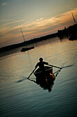 Man rowing boat in dusk on Lake Woerthsee, Bavaria, Germany, MR