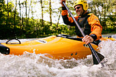 Man paddling on the Mangfall in his kayak, kayak weekend for beginners, Mangfall river, Upper Bavaria, Germany