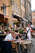People eating out in a street restaurant, Gamla Stan Old Town, Stockholm, Sweden