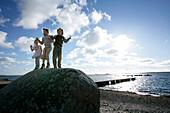 Three Kids standing on a big boulder, stone, on the beach, Torekov, Skane, Sweden
