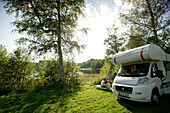 Motor home and family by the lakeshore, lake Nossen, Vimmerby, Smaland, Sweden