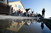 Cafes, quayside promenade, with reflection in a puddle, Visby, Gotland, Sweden
