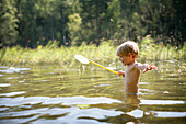 Boy (3-4 years) with a dip net standing in Lake Staffelsee, Upper Bavaria, Bavaria, Germany, MR