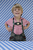 Boy (4-5 years) wearing leather trousers laughing at camera, Munsing, Upper Bavaria, Bavaria, Germany