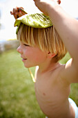 Boy (4-5 years) using a water lily leave as hat, Lake Staffelsee, Upper Bavaria, Bavaria, Germany