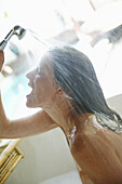 Mid adult woman using shower in bath, Styria, Austria