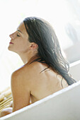 Mid adult woman with closed eyes relaxing in bathtub, Styria, Austria