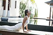 Woman doing Yoga exercises near a pool, Wellness, Relaxation, Health