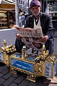 Shoeblack reading newspaper, Antalya, Turkish Riviera, Turkey
