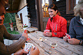 Young people playing cards in front of wooden cabin, Hohe Tauern National Park, Carinthia, Austria