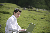 Mid adult man using a laptop, Heiligenblut, Hohe Tauern National Park, Carinthia, Austria