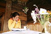 Woman reading a book in alp lodge, Heiligenblut, Hohe Tauern National Park, Carinthia, Austria