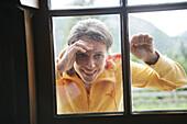 Woman looking through a window into alp lodge, Heiligenblut, Hohe Tauern National Park, Carinthia, Austria