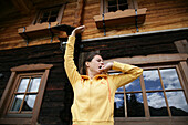 Woman yawning and stretching in front of alp lodge, Heiligenblut, Hohe Tauern National Park, Carinthia, Austria