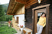 Woman standing on door of alp lodge, Heiligenblut, Hohe Tauern National Park, Carinthia, Austria