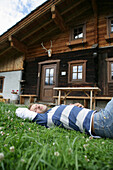 Man resting on grass in front of alp lodge, Heiligenblut, Hohe Tauern National Park, Carinthia, Austria