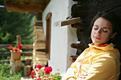 Woman with closed eyes sitting in front of alp lodge, Heiligenblut, Hohe Tauern National Park, Carinthia, Austria