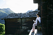 Woman reading a book in front of alp lodge, Heiligenblut, Hohe Tauern National Park, Carinthia, Austria
