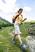 Female hiker on the way to a chapel, Heiligenblut, Hohe Tauern National Park, Carinthia, Austria