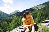 Woman sitting on a rock holding an apple, Heiligenblut, Hohe Tauern National Park, Carinthia, Austria