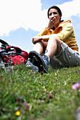 Woman sitting on grass while eating an apple, Heiligenblut, Hohe Tauern National Park, Carinthia, Austria
