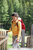 Woman passing a fence door, Heiligenblut, Hohe Tauern National Park, Carinthia, Austria