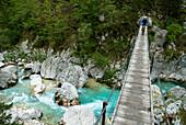 Mountainbiker auf einer Hängebrücke über Soca, Nationalpark Triglav, Slowenien