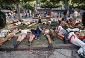 Taking a break from the party during San Fermin Festival. Pamplona. Navarre, Spain