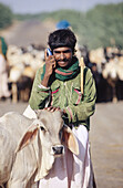 Single rural Indian man in green shirt with white cow and mobile phone.