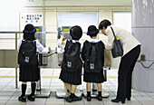 Some school girls are learning how to use a public telephone in the subways of Tokyo. Japan