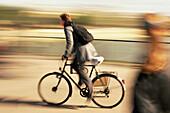 Aktivität, Außen, Bewegung, Brücke, Brücken, Dynamik, Eile, Eilig, Eine Person, Eins, Erwachsene, Erwachsener, Fahren, Fahrrad, Fahrräder, Fahrradfahren, Farbe, Ganzkörper, Ganzkörperaufnahme, Horizontal, Mensch, Menschen, Pedale, Profil, Profile, Radfah