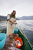 Fisherman at work on the lake. Iseo lake. Lombardia. Italy.