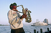 Jazz musician playing saxo on Mississipi bank and steamboat Natchez in background. Louisiana, USA