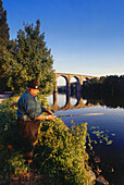 Angler fishing, Railway viaduct in the background, Herdecke, Ruhr Valley, Ruhr, Northrhine Westphalia, Germany