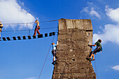Climbers climbing up a tower at Hütte Meiderich, Public Park in Duisburg North, Duisburg, Ruhr Valley, North Rhine Westphalia, Germany